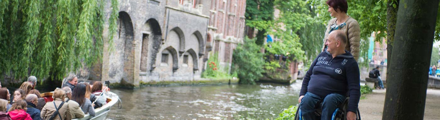 Couple in wheelchair walking along canals in Bruges